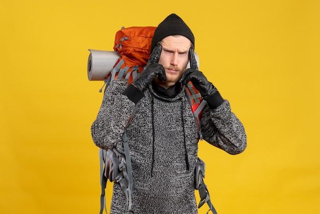 Mężczyzna autostopowicz w skórzanych rękawiczkach i plecaku kładący palce na skroni