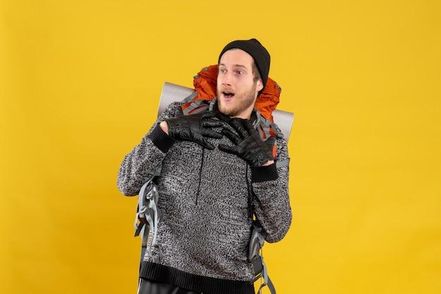 Mężczyzna autostopowicz w skórzanych rękawiczkach i plecaku kładący ręce na piersi