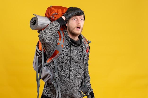Mężczyzna autostopowicz w skórzanych rękawiczkach i plecaku patrzący na coś