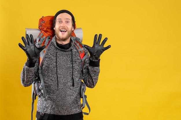 Mężczyzna autostopowicz w skórzanych rękawiczkach i plecaku podnoszącym ręce