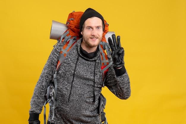 Mężczyzna autostopowicz w skórzanych rękawiczkach i plecaku pokazującym trzy palce