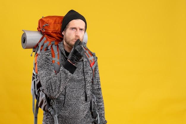 Mężczyzna autostopowicz w skórzanych rękawiczkach i plecaku robiący znak shh