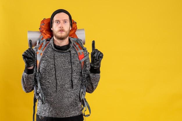 Mężczyzna autostopowicz w skórzanych rękawiczkach i plecaku skierowanym palcami do góry
