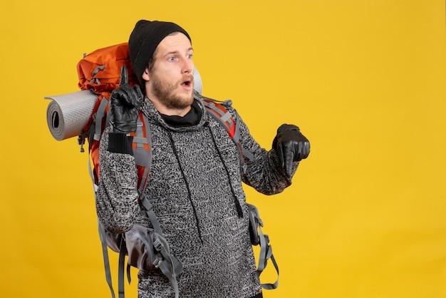 Mężczyzna autostopowicz w skórzanych rękawiczkach i plecaku skierowanym w górę i w dół