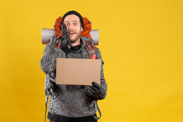 Mężczyzna autostopowicz w skórzanych rękawiczkach i plecaku trzymającym czysty karton