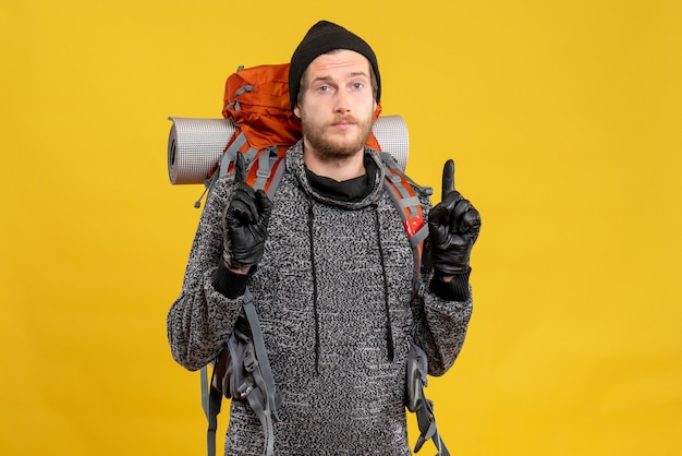 Mężczyzna autostopowicz w skórzanych rękawiczkach i plecaku wskazującym palce w górę