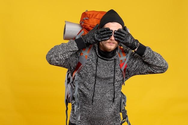 Mężczyzna autostopowicz w skórzanych rękawiczkach i plecaku zakrywającym oczy rękami