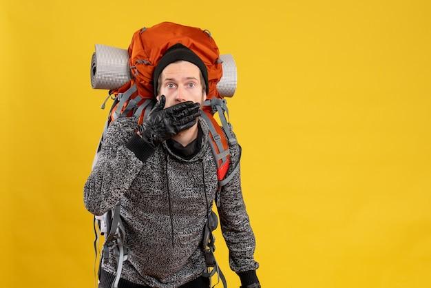 Mężczyzna autostopowicz w skórzanych rękawiczkach i plecaku zakrywającym usta dłonią