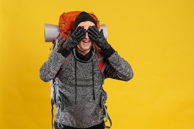 Mężczyzna autostopowicz w skórzanych rękawiczkach i plecaku zasłaniającym oczy dłońmi