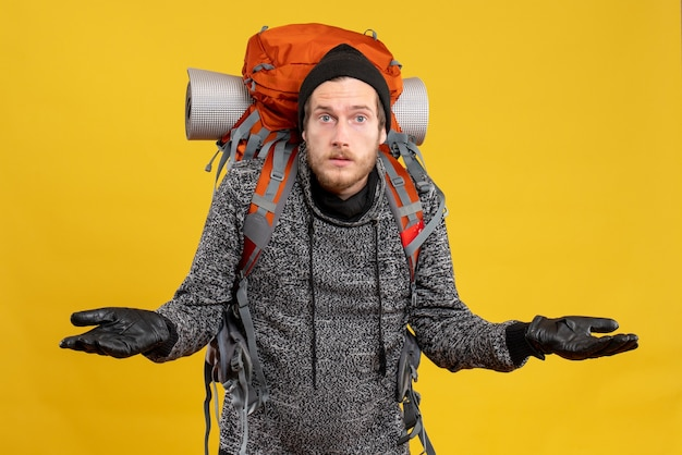 Mężczyzna autostopowicz ze skórzanymi rękawiczkami i plecakiem ciekawi