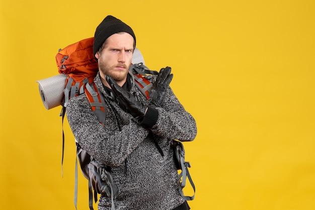 Mężczyzna autostopowicz ze skórzanymi rękawiczkami i plecakiem krzyżującym ręce odrzucając coś