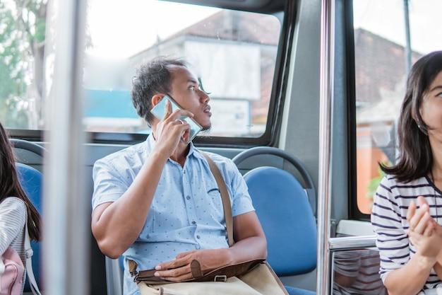 Mężczyzna azjata korzystający z telefonu komórkowego podczas jazdy autobusem publicznym lub metrem