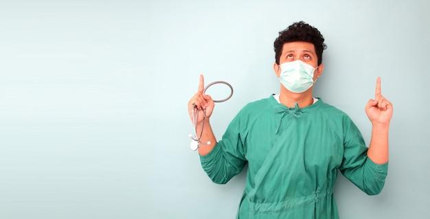 Mężczyzna azjatycki chirurg lekarz, chirurg pokazujący stetoskop noszący maskę chirurga, nad niebieską ścianą, czuje się zaskoczony, patrząc w górę i wskazując palcami i uniesionymi rękami.