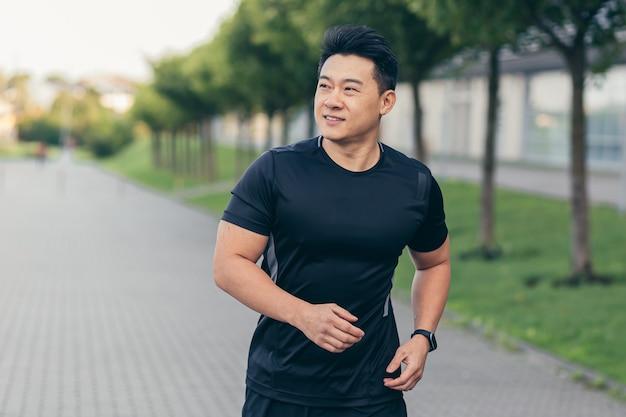 Mężczyzna azjatycki sportowiec biegający w parku w plecaku przed pracą, biegający w parku w pobliżu stadionu