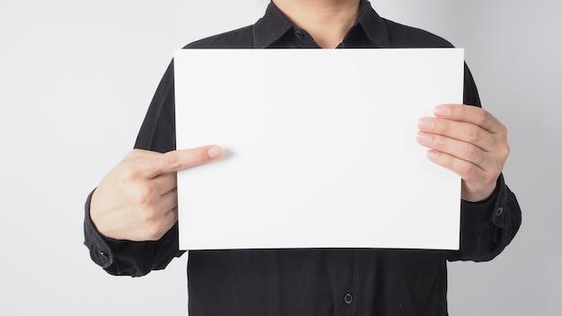 Mężczyzna azjatycki trzymać czysty papier ręką jest punkt i nosić czarną koszulę na białym tle.