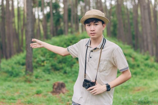 Mężczyzna azji nosi koszulę, a kapelusz wskazuje las w lesie