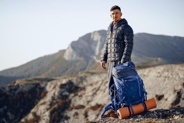 Mężczyzna backpacker w sprzęt turystyczny stojący na szczycie góry