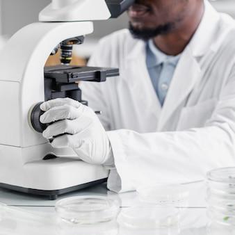 Mężczyzna badacz analizujący pod mikroskopem w laboratorium biotechnologii