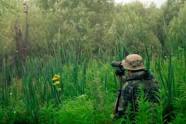 Mężczyzna badacz przyrody prowadzi obserwację terenową przez lunetę stojącą wśród wysokiej trawy
