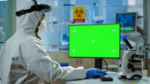 Mężczyzna badacz w kombinezonie patrzący na komputer z kluczem chrominancyjnym w nowocześnie wyposażonym laboratorium. zespół mikrobiologów prowadzących badania nad szczepionkami piszący na urządzeniu z zielonym ekranem, na białym tle, makieta wyświetlacza.