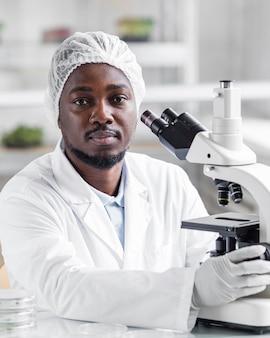 Mężczyzna badacz w laboratorium biotechnologicznym z mikroskopem i rękawiczkami