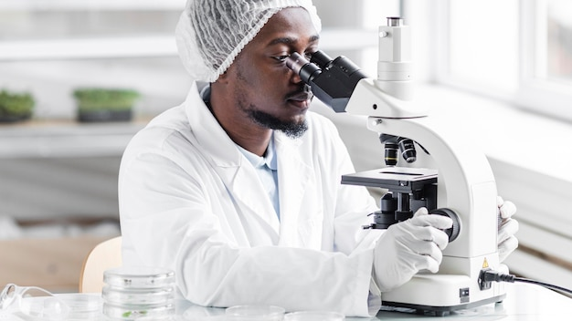 Mężczyzna badacz w laboratorium biotechnologicznym z mikroskopem