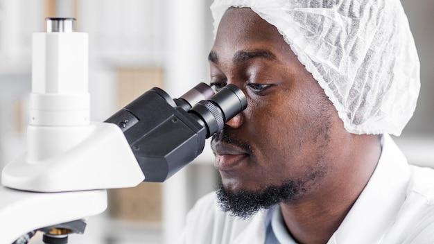 Mężczyzna badacz z mikroskopem w laboratorium biotechnologii