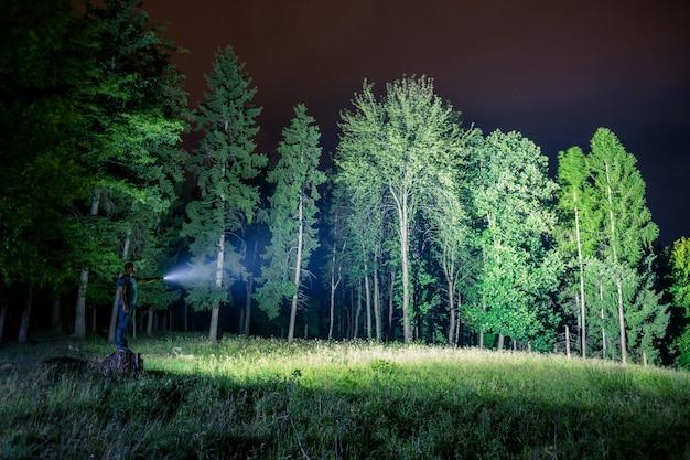 Mężczyzna badający las z latarką w nocy