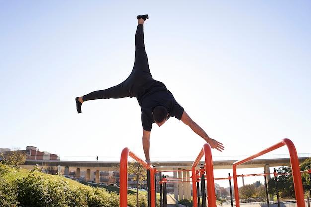 Mężczyzna balansując jedną ręką, stojąc na rękach na barze, w barze w mieście. ćwiczenia na świeżym powietrzu. pojęcie zdrowego trybu życia, sportu, treningu, kalisteniki.