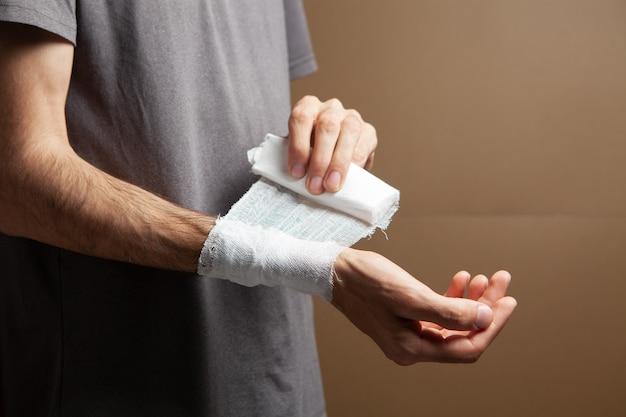 Mężczyzna bandażuje rękę na brązowym tle