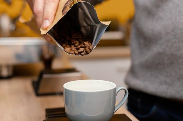 Mężczyzna barista odlewania ziaren kawy w filiżance