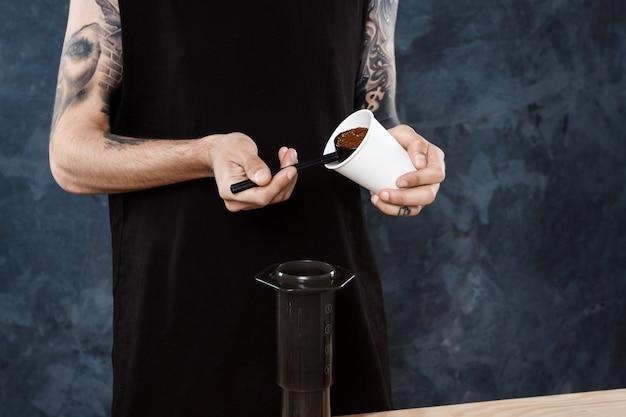 Mężczyzna barista parzenia kawy. alternatywna metoda aeropress.