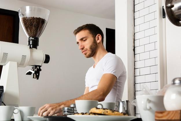 Mężczyzna barista pracuje za ladą