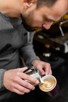 Mężczyzna barista przygotowuje kawę