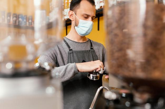 Mężczyzna barista sprzątający profesjonalny ekspres do kawy