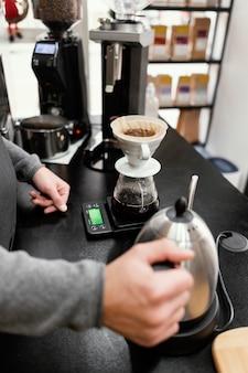 Mężczyzna barista trzyma czajnik i przygotowuje się do zrobienia kawy