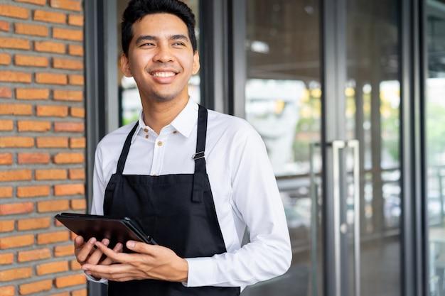 Mężczyzna barista trzymając tablet i stojąc na zewnątrz kawiarni kawiarni