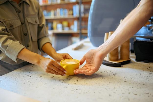 Mężczyzna barista w fartuchu daje kawę kobiecie w kawiarni