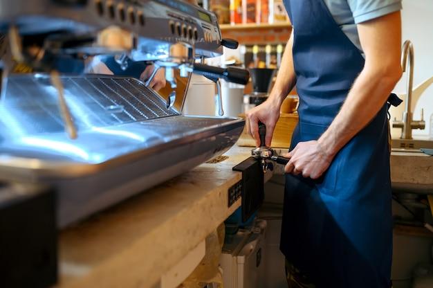 Mężczyzna barista w fartuchu przygotowuje kawę na maszynie w kawiarni