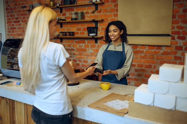 Mężczyzna barista w kawiarni, klientka płaci za zamówienie