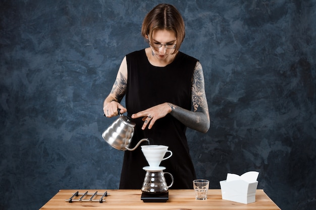 Mężczyzna barista warzenia kawy