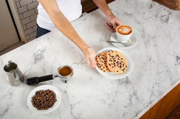 Mężczyzna barista z ciasteczkami i cappuccino