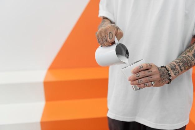Mężczyzna barista z tatuażami dodający mleka do kawy