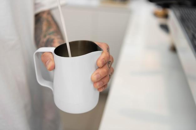 Mężczyzna barista z tatuażami nalewający mleko w filiżance