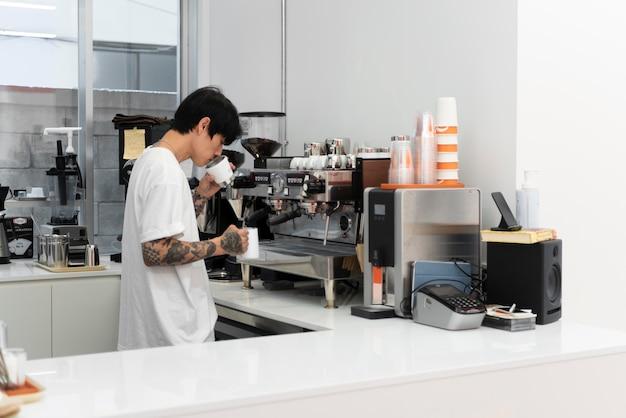 Mężczyzna barista z tatuażami pachnący świeżo mieloną kawą w filiżance