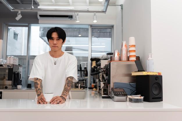 Mężczyzna barista z tatuażami serwujący kawę przy ladzie