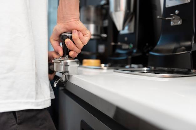 Mężczyzna barista z tatuażami w pracy przy ekspresie do kawy