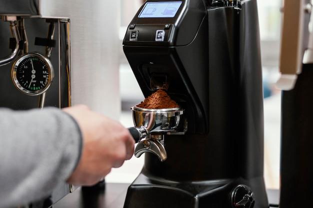 Mężczyzna barista za pomocą filiżanki ekspresu do kawy