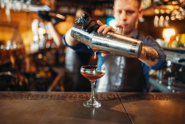 Mężczyzna barman leje drinka z shakera
