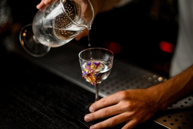 Mężczyzna barman leje koktajl z miarki z sitkiem do szklanki ozdobionej kwiatami